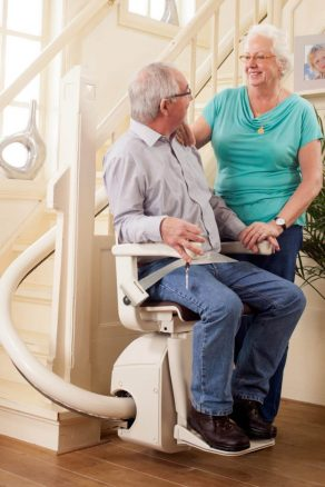 A man on a curved stairlift with lady standing by.
